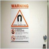 Дверь в кабинет МРТ с предупреждающими надписями о сильном магнитном поле, чем вреден МРТ